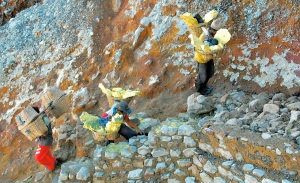 Ijen miners carrying loads up the steep trail—Caroline Helbig